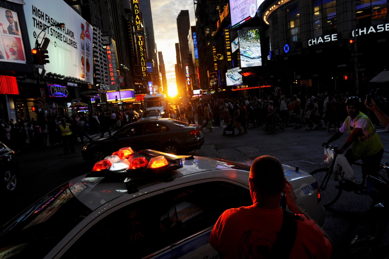 "A police car passes, telling people to leave the street as the sun sets over Manhattan aligned exactly with the streets in a phenomenon known as ""Manhattanhenge"", in New York City, U.S., July 11, 2016. REUTERS/Mark Kauzlarich"