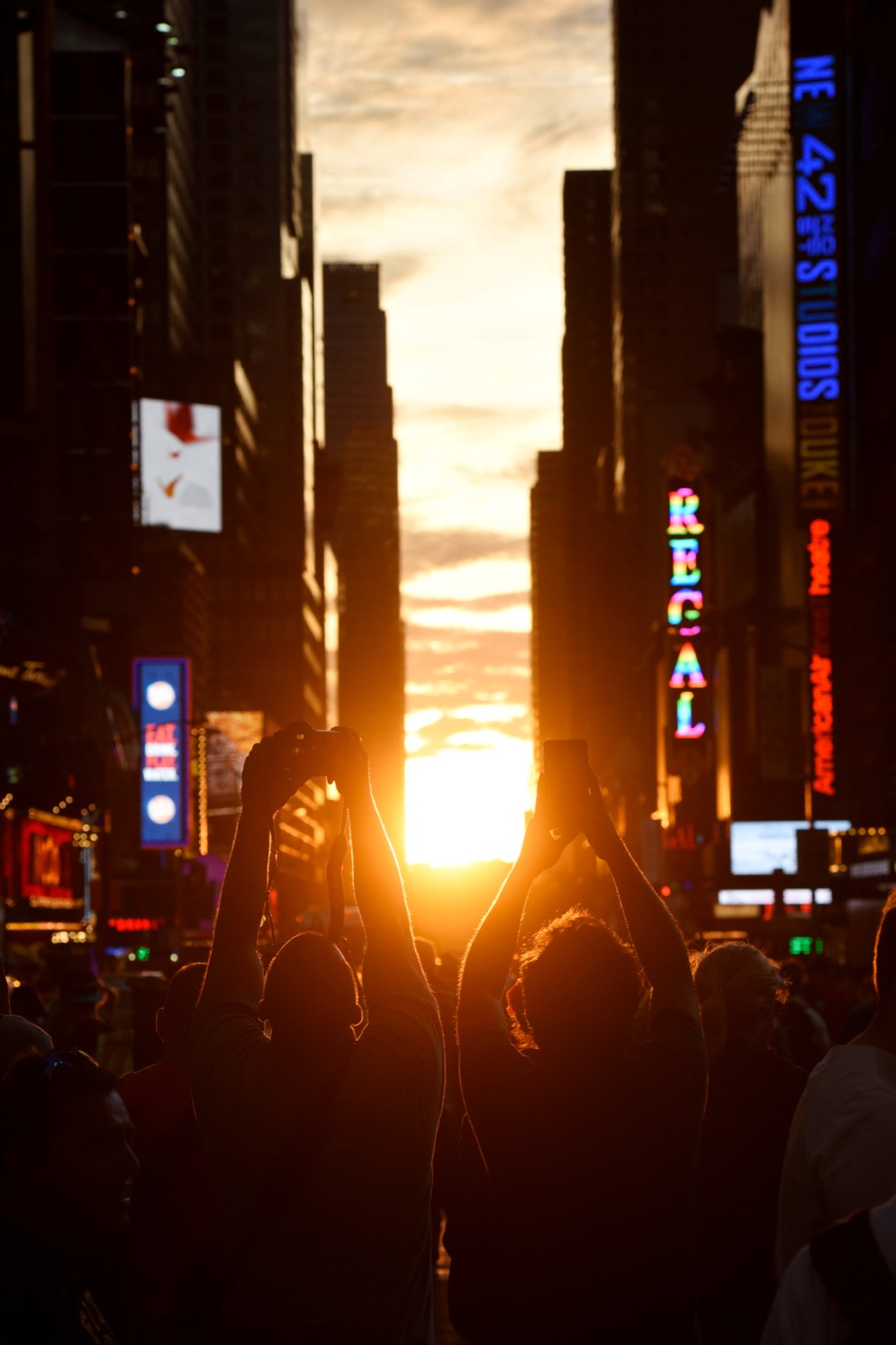 "Two men take pictures as the sun sets over Manhattan aligned exactly with the streets in a phenomenon known as ""Manhattanhenge"", in New York City, U.S., July 11, 2016. REUTERS/Mark Kauzlarich"