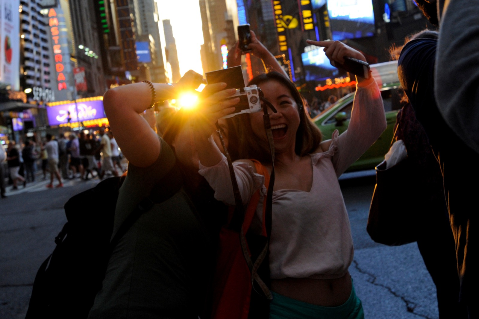 "People take a selfie as the sun sets over Manhattan aligned exactly with the streets in a phenomenon known as ""Manhattanhenge"", in New York City, U.S., July 11, 2016. REUTERS/Mark Kauzlarich"